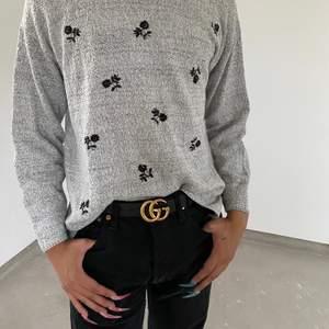 Gullig grå stickad tröja med svarta blommar på med två slitsar vid höfterna! Fraktar för extra kostnad