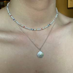 Ett jättegulligt pärlhalsband av vita vaxade glaspärlor och färglada glaspärlor! Går att förlänga med en kedja✨ Frakt INGÅR i priset (69kr + 11kr frakt)❤️