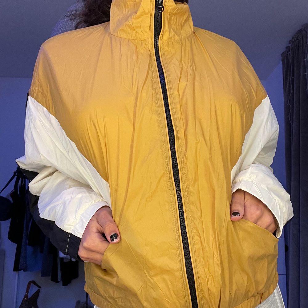 En gul/guldig tunn vindjacka som passar bra för våren eller för att piffa upp sin outfit till något extra! Fungerar lika bra som en jacka eller kofta😊. Jackor.