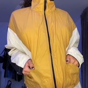 En gul/guldig tunn vindjacka som passar bra för våren eller för att piffa upp sin outfit till något extra! Fungerar lika bra som en jacka eller kofta😊