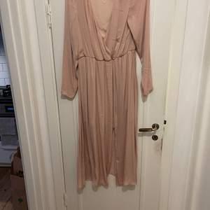 Långärmad puderrosa klänning med slits i kjolen, underkjol till hälften av låren sen lite mer genomskinligt tyg. Köptes för ett bröllop 2018 men var tyvärr för liten, aldrig använd.