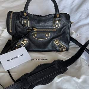 """Säljer denna svarta Balenciaga väska med gulddetaljer. Den är mycket sparsamt använd och därför i fint skick. Väskmodellen heter """"Balenciaga mini city"""". Nypris ligger på ca 13 000 kr. Svarar inte på skambud"""