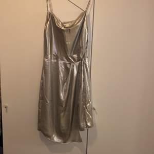 Miniklänning från H&M! Detaljer med metallictråd. Silver färg! Knäppning i sidan med dragkedja. Använda en gång!!!! Det ser ut som nytt! 🙂