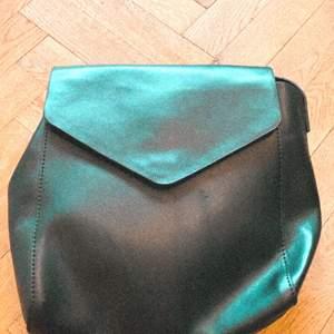 Svart ryggsäck i fuskläder
