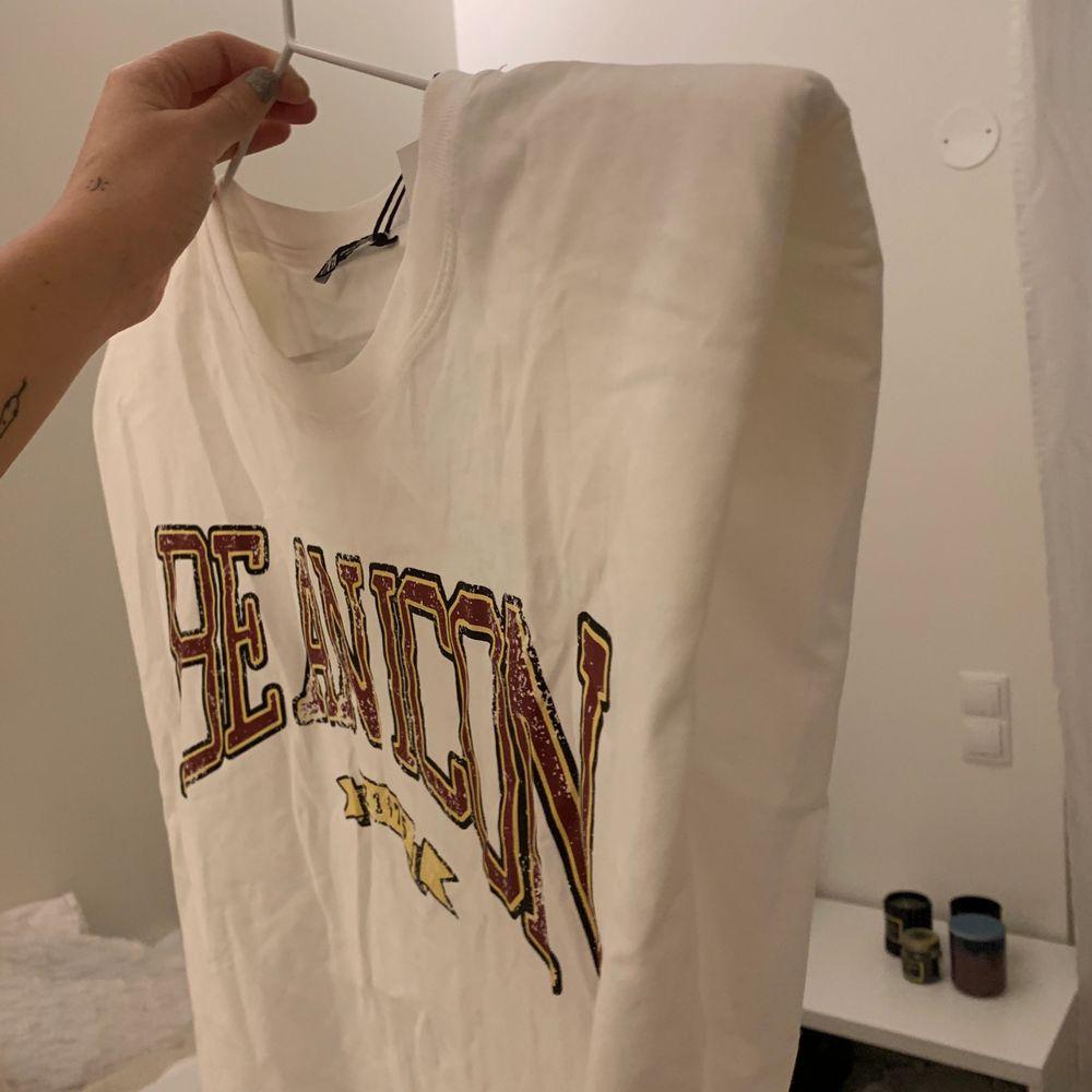 Vit T-shirt med axelvaddar och tryck från Zara! Aldrig använd med lappen kvar, säljer då den inte kommer till användning! . T-shirts.