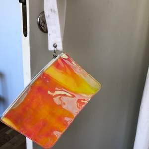 En liten clutch väska som skimrar i olika färger. Lite fläckar på handtaget...