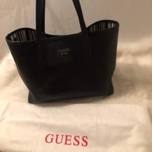 En större Guess väska som går att ha på två vis, svart läder. Liten pouch medföljer!