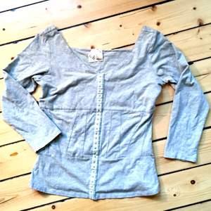 Grå långärmad tröja från Carin Wester med snygga sömmar i ett mönster runt midjan. Aldrig använd, säljer pga för liten!  Hör av Dig om du vill veta något mer:)