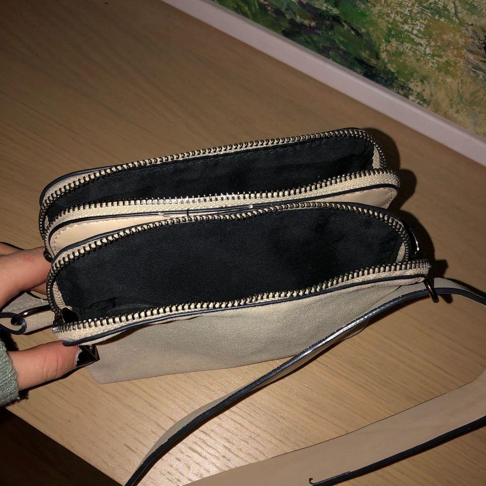 Säljer denna beiga väska från Lindex. Använd en del förra året men det finns inga defekter på väskan. Man kan justera axelbandet och både ha den som en axelremsväska och som en cross body bag. Den har två fack.. Väskor.