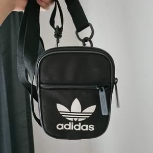 Fin liten väska där man kan förvara mobilen, plånboken mm. Har två st fack. Knappt använd.                               Längd/höjd?: 15,5 cm. Bredd: 11,5 cm                                         Frakt tillkommer