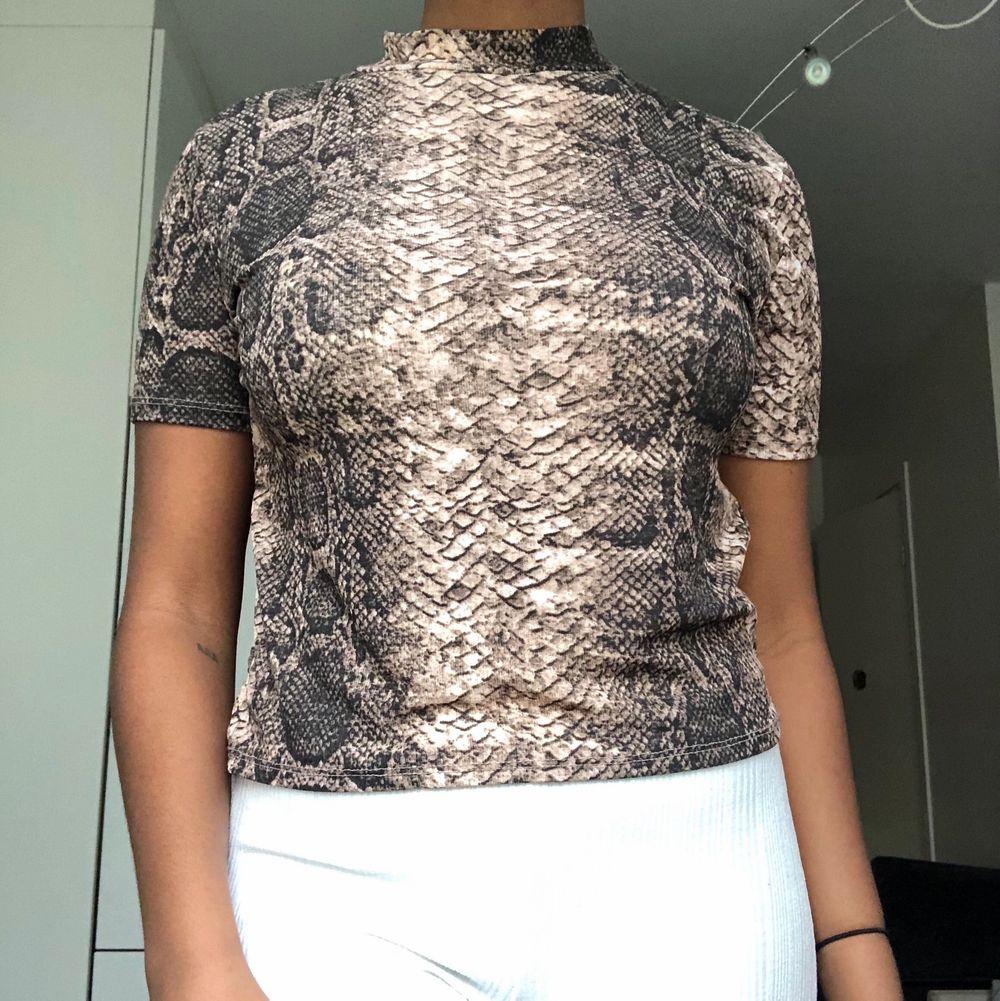 """En T shirt från zara med ormskinnstryck, den har en liten krage som ger tröjan en liten """"ummmpfh"""". Fett snygg på med halsband över. Använd ett fåtal gånger dock i väldigt bra skick!. Toppar."""