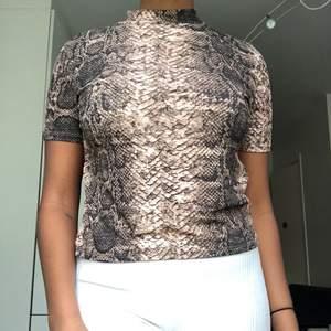 """En T shirt från zara med ormskinnstryck, den har en liten krage som ger tröjan en liten """"ummmpfh"""". Fett snygg på med halsband över. Använd ett fåtal gånger dock i väldigt bra skick!"""
