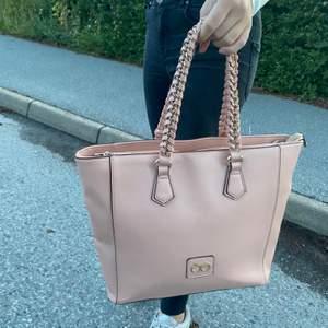 En rosa väska som inte kommer till användning längre. Den har guld detaljer (inte äkta guld) köpte den för 500 men säljer för 200kr. Köpare står för frakt.