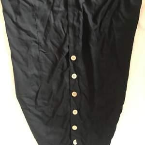 En kjol som kan knäppas upp hela vägen. Är lite öppen framme längst ner och är använd en gång och säljer pågrund av att den är för stor i midjan. Är lite skrynkig efter ja tvätta den. Måste strykas.