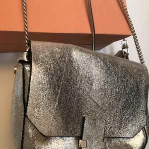 Silvrig liten väska med axelband, perfekt att pigga upp en svart outfit till vardags eller fest 🤩 köparen står för frakt