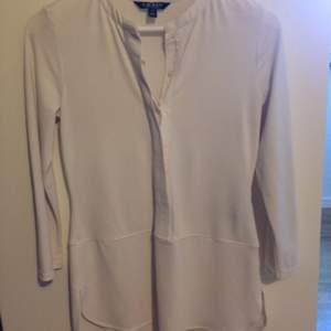 Lauren by Ralph Lauren blus i vit trikå vilket gör den elastisk. Dold knappslå halv framtill och rundhalsad kraglös. Ärm 3/4 smal. Väldigt fin passform och i mycket gott skick. Tvättad 2 ggr och lite använd. Köpt på best of brands 2016.