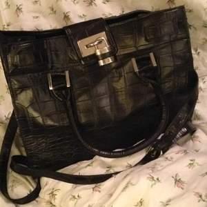 Snyggt stilren handväska. Faux läder. Ormskinnsmönster (se bild 3). Snygga detaljer, t.ex. hänglås. Axelremmen går att haka av. Fråga gärna om du undrar något!  Bredd: 32 cm Höjd: 25 cm Djup: 17