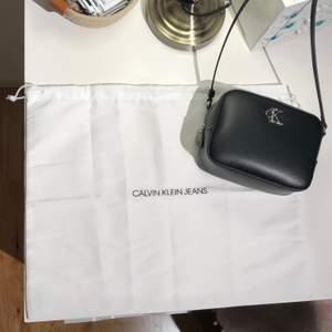 """En svart fin ny axelremsväska från CKJ (ja den är äkta se bild p """"kvittot"""" el vad man kallar det mappen med bevis i alla fall) Fin och så men har inte använt på länge och behövde rensa. Tyvärr så behöver jag då sälja denna. Den är som sagt ny och använd 2 ggr. Köptes från CK hemsida se bild på CK-mappen. Köptes för 900kr och är i nyskick, har inga som helst märken och är som ny. Kan både frakta mötas och så kan ni hämta i sthm nacka. Ni kan få flera bilder om ni vill det är bara att fråga! Alla bilder fick ej olats här. (Fråga om du vill veta fraktpris oxå)👍🏼☺️"""