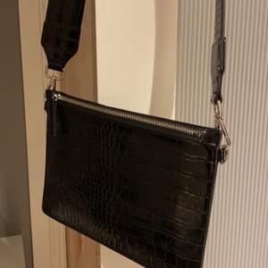 """Säljer nu denna väska som jag använt fåtal ggr! Den är liten och sleek men man får plats med allt man behöver! Den är av """"ormskin"""" och är skitsnygg men kommer inte till användning..  Den är från Carin Wester och är köpt på Åhléns"""