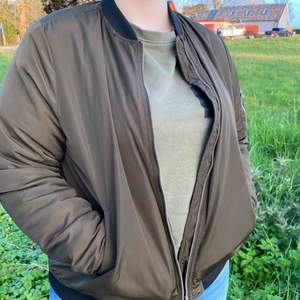 Military green bomber jacket with black details. 100% polyester. Used the whole summer of 2018, still in really good shape.  59kr shipping