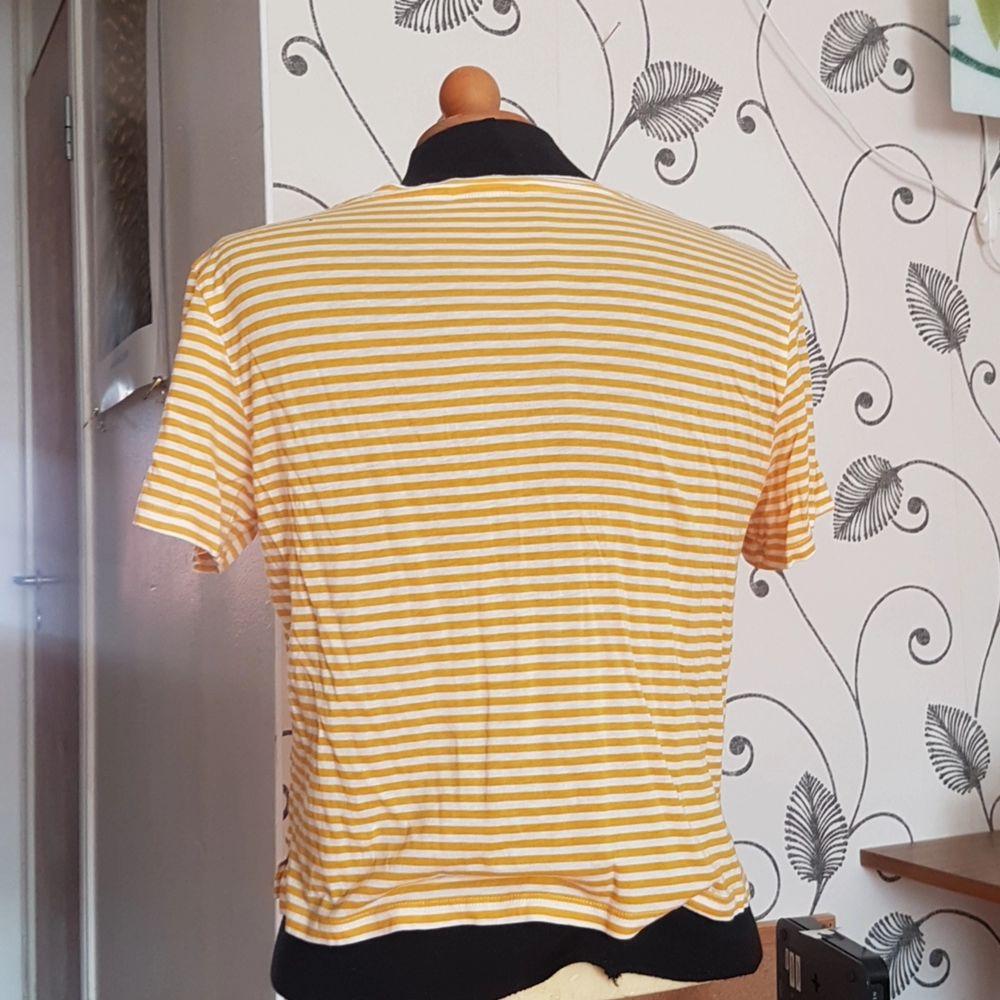 Denna gul-vit-randiga t-shirt från Monki säljes då den inte längre används. Den har ett litet hål vid vänster axel som går att laga utan några problem. Passar både S och M! Skönt material!. T-shirts.