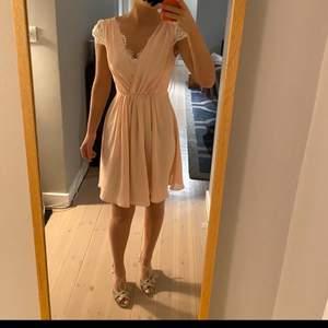 En så fin babyrosa klänning från By Malina, klänningen har ljusa spetsdetaljer i ryggen och på ärmarna. Den är sparsamt använd, alltså i gott skick, och en så fin klänning till sommarhalvåret! storlek XS, modellen är 165 cm för referens