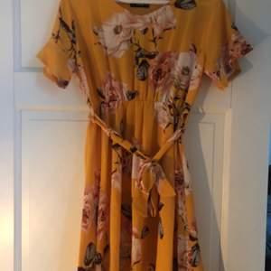 Blommig gul klänning i storlek M sälja för 150 kr. Aldrig använd. Frakt ingår.