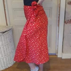 Vit blommig röd kjol som man knyter vid midjan. 65% bomull 35%polyester