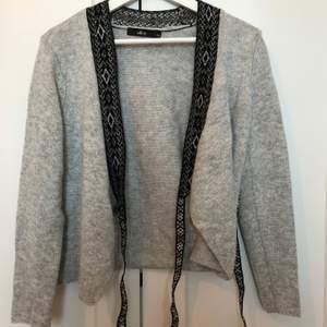 Stickad tröja ifrån Ellos som är grå med svarta detaljer, plagget är endast använt fåtal gånger och är i fint skick. Köparen står för frakt 69kr