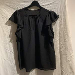 Söt svart blus från H&M med små svarta prickar och volanger vid axlarna.  Använd få gånger och är i bra skick, den är lite genomskinlig högst upp till både på fram och baksida (kolla sista bilden)
