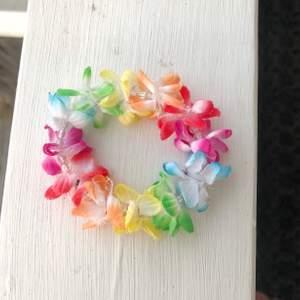 Typiskt 2000s armband med hawaiiblommor på i olika färger. Köpt tidigt 2000-tal och i bra skick.