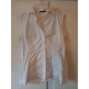 En fin vit skjorta/blus från Hugo Boss. Det öppnad med dragkedjor i båda sidorna och tyget är något stretching men lite genomskinlig, därav min gissning att det är en under shirt i
