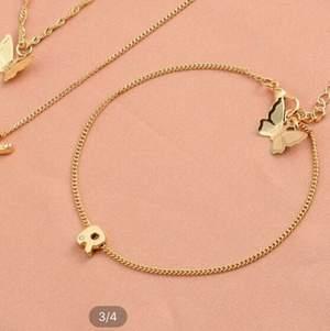 Guldfärgat armband med en fjärilsdetalj 🦋 och ett R frakten är inkluderad