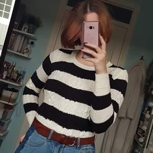 Varm stickad tröja med flätmönster på framsidan och muddar i ärmarna