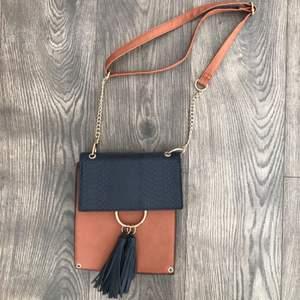 Säljer denna väska i brun och blå färg.