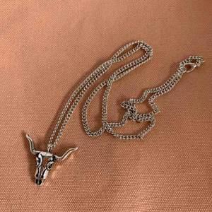 Kedja, halsband med buffelskalle i silverfärgad metall. Mått: berlock ca 3x2 cm. Skick: nyskick / oanvänt! Frakt ingår i denna annons.