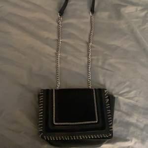 Säljer denna svarta väska med kedja då den inte kommer till andvändning😊den är lite läder imiterad och på vissa ställen lite som mocka💕