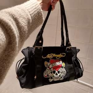 En trendig ed Hardy väska! Rymlig och bra skick, har också krokodilskinnsimitation på banden. Superfin men inte min stil riktigt🥰 ej säker på fraktkostnaden ännu! Kan ej garantera äkthet då jag inte är så insatt på märkesgrejer😅