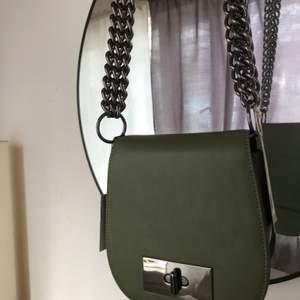 Helt oanvänd, grön NA-KD Väska med chunky chains. Väskan har en innerficka och en ytterficka på baksidan för t.ex kort. Säljes för 150kr + frakt