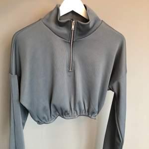 Supersnygg grå kort tröja i ribbstickning med dragkedja framtill. Använd 1 gång, Mkt bra skick. Köpt för 300kr på Asos (slutsåld).