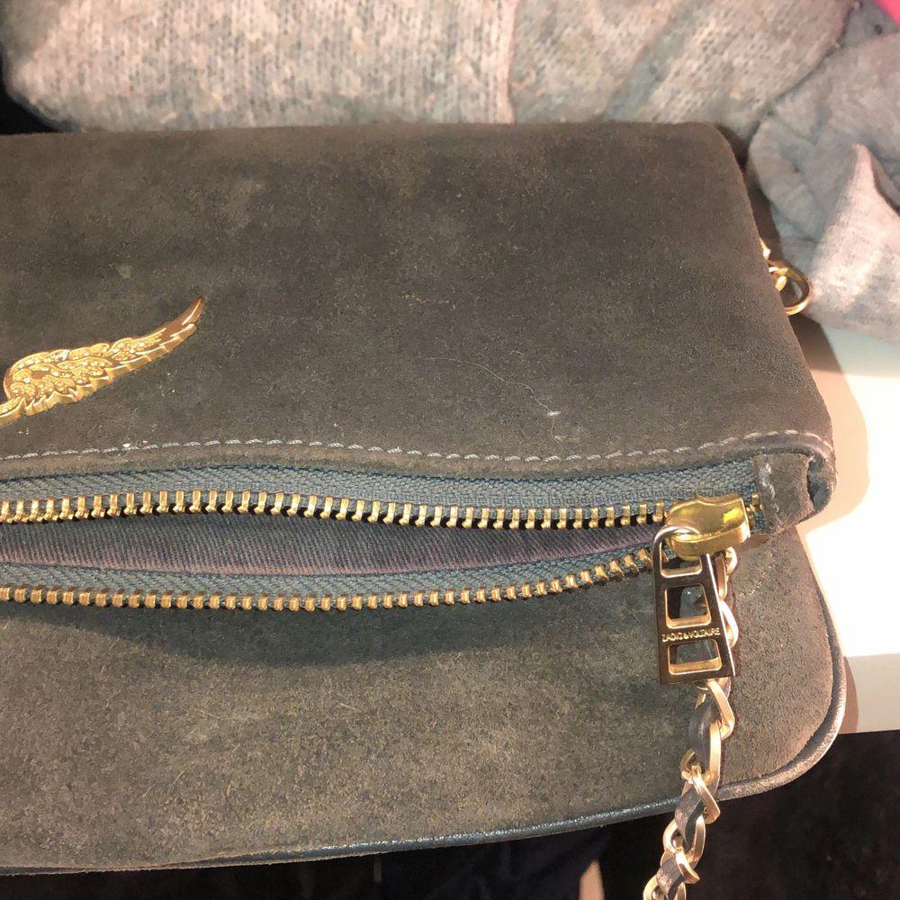 Bra skick. Köpt cirka 3 år sedan. Gråblå färg med guld detaljer. Antar att det är läder?. Väskor.