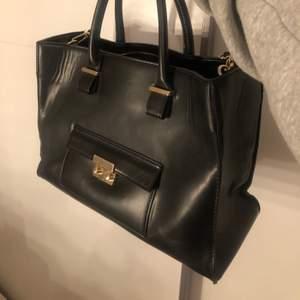 En svart rymlig väska från H&M, med gulddetaljer. Använd flertalets gånger och har lite slitage på sidorna. Dock fortfarande fin.
