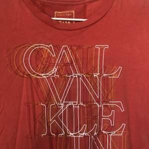 Vintage tshirt från kalven Klein, en Persiko-röd färg, och en oversize passform. Storlek L. Köpt förra året utomlands på vintagebutik. Använder inte längre. Frakt 20kr/mötas upp