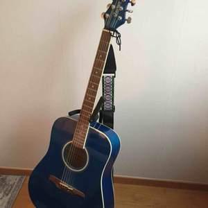Stålsträngad akustisk gitarr från märket Guvnor i fint skick. Golvställ, stämapparat, capo och axelrem ingår, hämtas i Täby