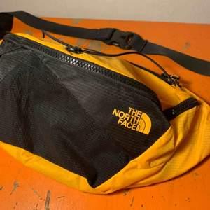 En större The North Face fannypack. Stl L, rymlig med totalt 5 fack. Fin varm gul färg med svarta detaljer. Aldrig använd, cond därav 10/10!