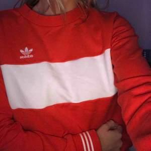 Så snygg röd sweatshirt från Adidas!!  Har 3 vita streck längs muddarna på armarna & vid midjan. Även ett streck på framsidan vid bröstet. Köpt i USA för 600kr.  Köparen står för frakten 🤗