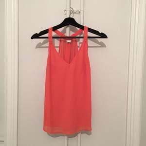 Söt topp, skulle säga att den är orange/rosa/korall-färgad!