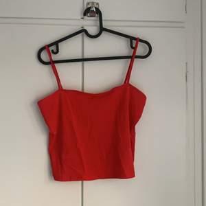Rött croppat linne med rak urringning. Sparsamt använd. Den är lite skrynklig nu då den legat i garderoben länge.
