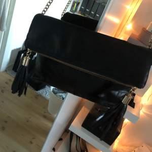 En svart väska i skinn imitation från med två stora fack inne och två fransar på utsidan. Väskan kommer från Oasis och har använts ett antal gånger, utan att få några större skador. Dragkedjorna är guldiga. Du står för frakten utöver priset👜💞 Jag kan inte stå för postens slarv
