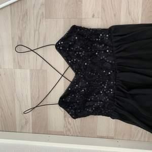 Svart kortklänning köpt från Nelly.com med tunna band och paljetter.